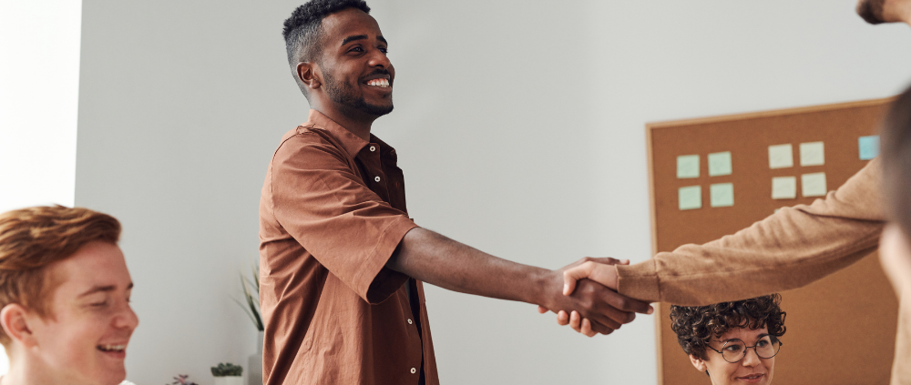 Developing a Bulletproof Go-To-Market Strategy. Smiling business man shakes hand of another business man.